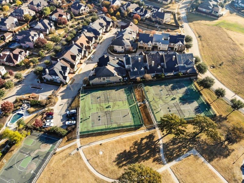 Pistas de tenis residenciales de la visión superior con los jugadores en la mañana del otoño en Tejas del norte, América imagen de archivo libre de regalías