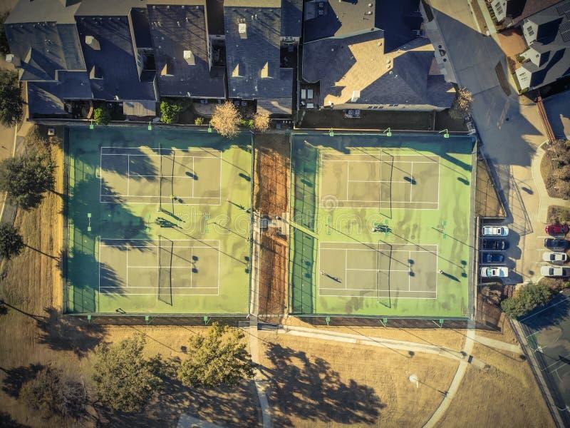Pistas de tenis residenciales de la visión superior con los jugadores en Tejas, América foto de archivo libre de regalías