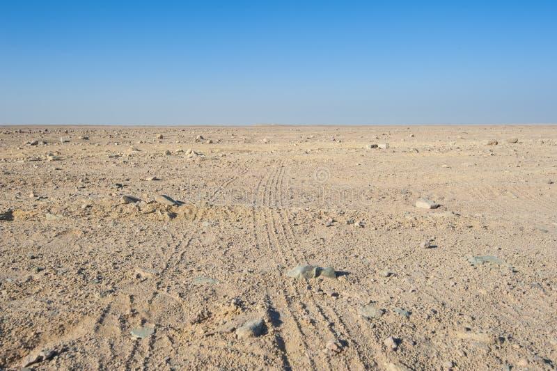 Pistas de vehículo a través de un desierto árido imagenes de archivo
