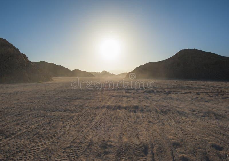 Pistas de vehículo a través de un desierto árido fotografía de archivo