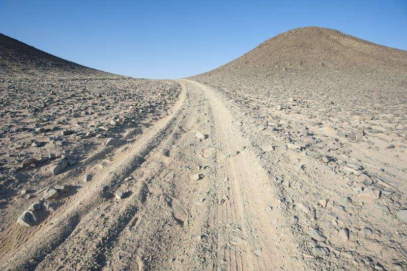 Pistas de vehículo a través de un desierto árido fotografía de archivo libre de regalías