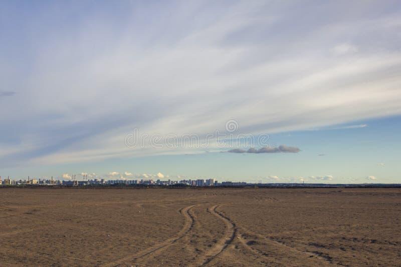 Pistas del coche en el desierto arenoso en el fondo de una ciudad moderna con los tubos de fábricas debajo del cielo azul fotografía de archivo libre de regalías