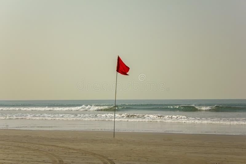 Pistas del coche en una playa arenosa amarilla cerca de una bandera roja que prohíbe nadar en medio de olas oceánicas debajo de u imagenes de archivo