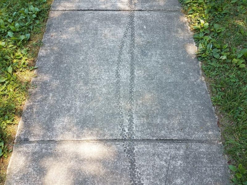 Pistas del neumático de la bici en el cemento gris fotos de archivo
