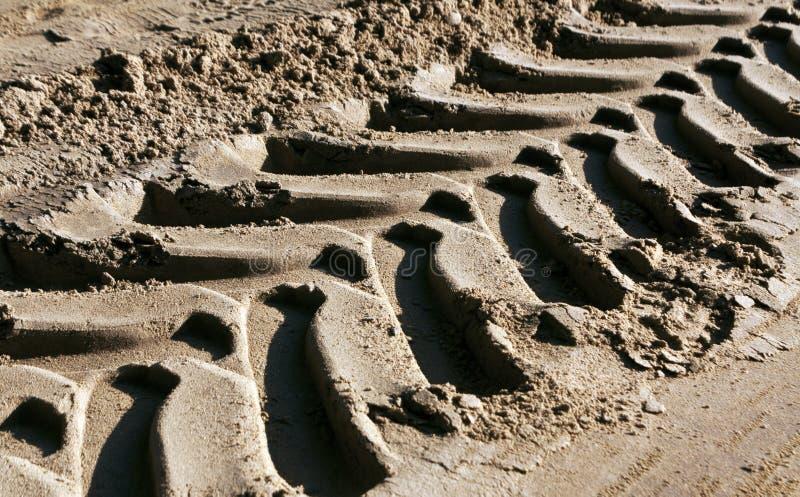 Pistas del neumático en la arena con efecto de la falta de definición imágenes de archivo libres de regalías