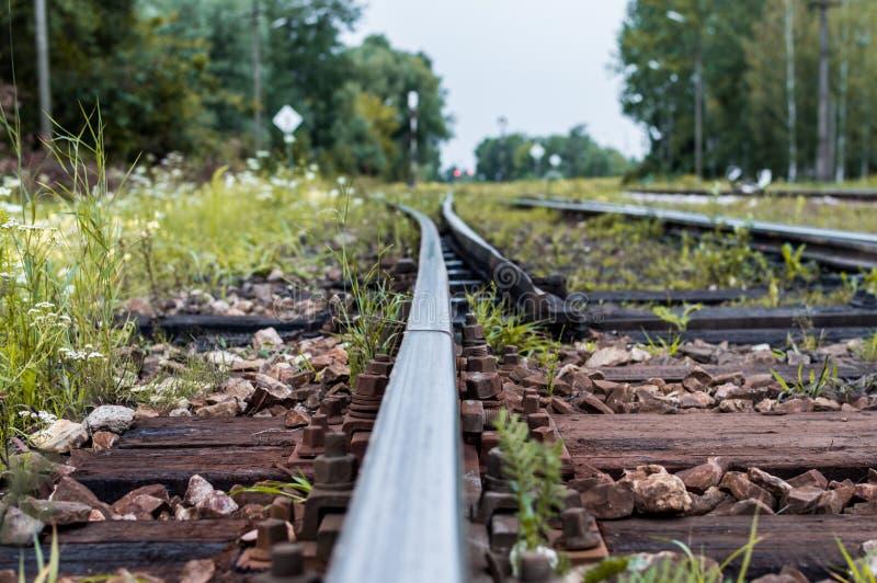 Pistas ferroviarias viejas y grava que llevan en la distancia infinita con el foco selectivo imagen de archivo