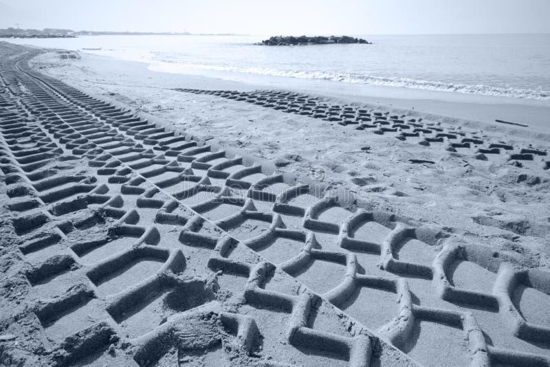 Pistas pesadas del neumático en la arena imagen de archivo