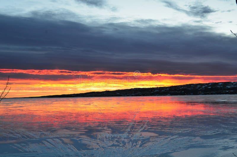 Pistas reflectoras de una nieve de la salida del sol en el lago congelado imagen de archivo libre de regalías