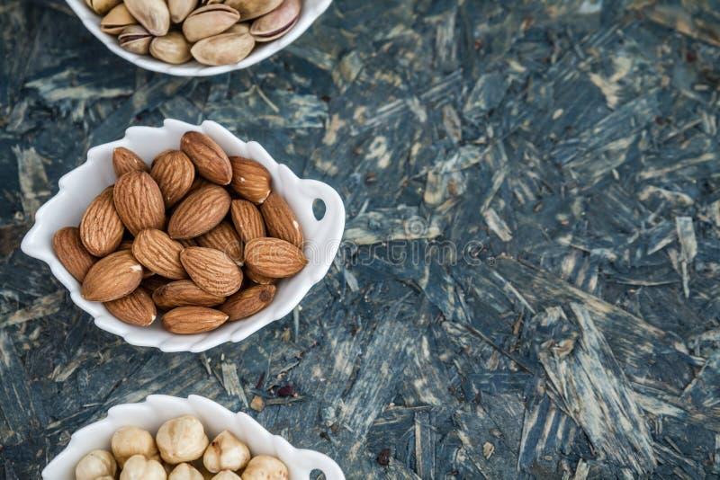 Pistascher, mandlar och hasselnötter i vita bunkar royaltyfri foto