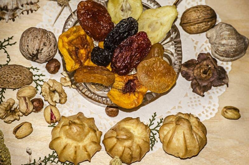 Pistazien, Nüsse, Haselnüsse nahe einer Kristallrosette mit Trockenfrüchten, Eclairs, Zimt auf einer dargestellten Serviette stockbild