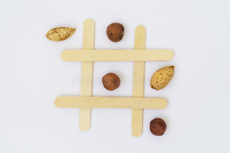 Pistazien und Trockenfrüchte auf dem Feld für das Spiel der Tic-TACzehe auf einem weißen Hintergrund lizenzfreies stockbild