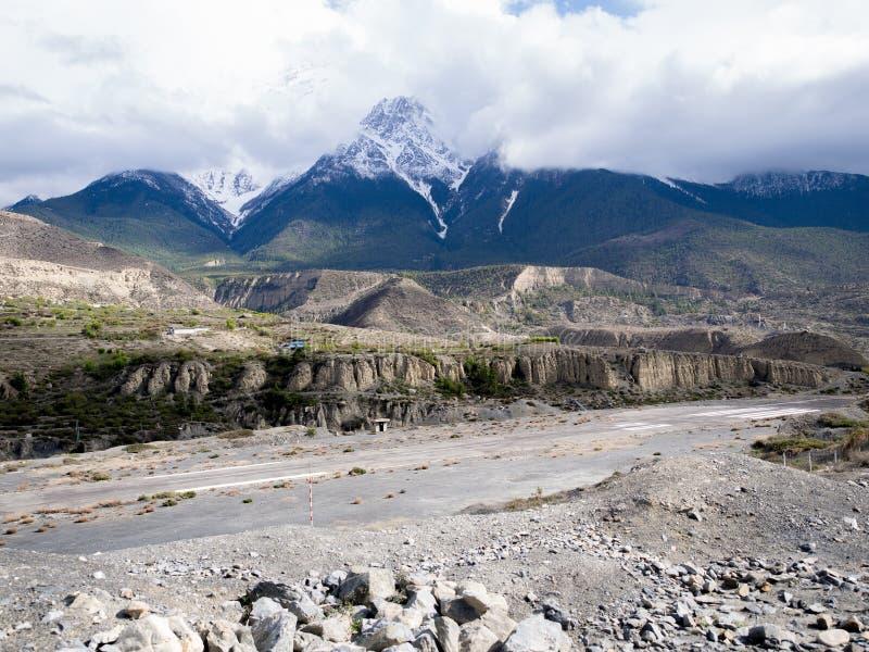 Piste d'aéroport dans la vallée de montagne avec la montagne obscurcie de neige de temps comme fond, images libres de droits