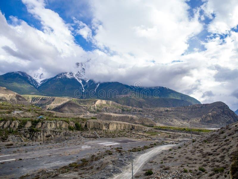 Piste d'aéroport dans la vallée de montagne avec la montagne obscurcie de neige de temps comme fond, Jomsom images stock