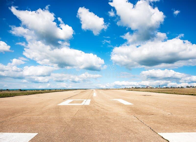 Piste, piste d'atterrissage dans le terminal d'aéroport avec l'inscription sur le ciel bleu avec le fond de nuages Concept d'avia photo stock
