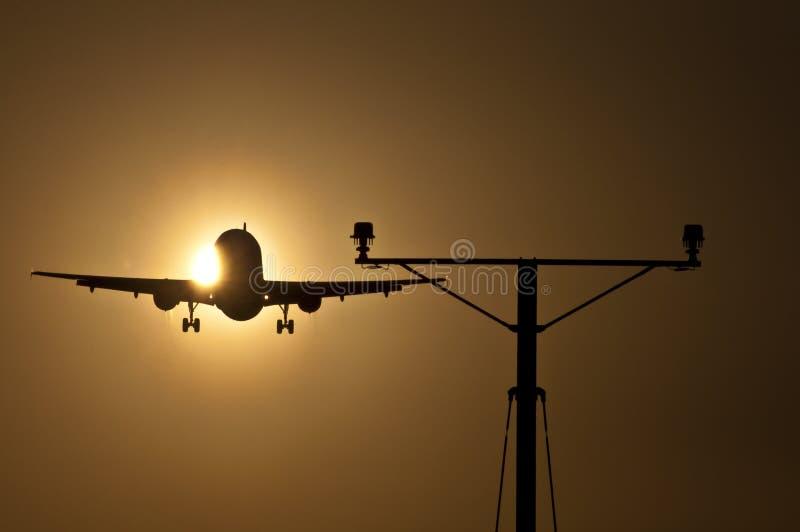 Piste de approche d'avion de passagers au coucher du soleil image stock