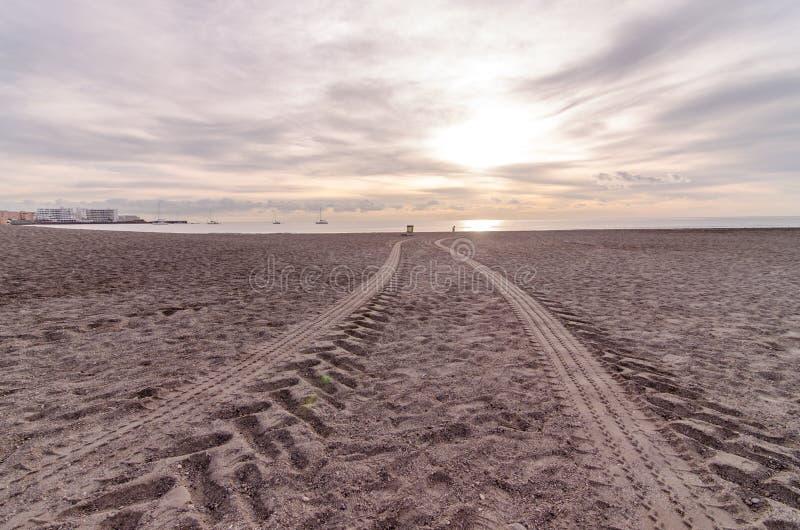 Piste della rotella nella sabbia immagine stock