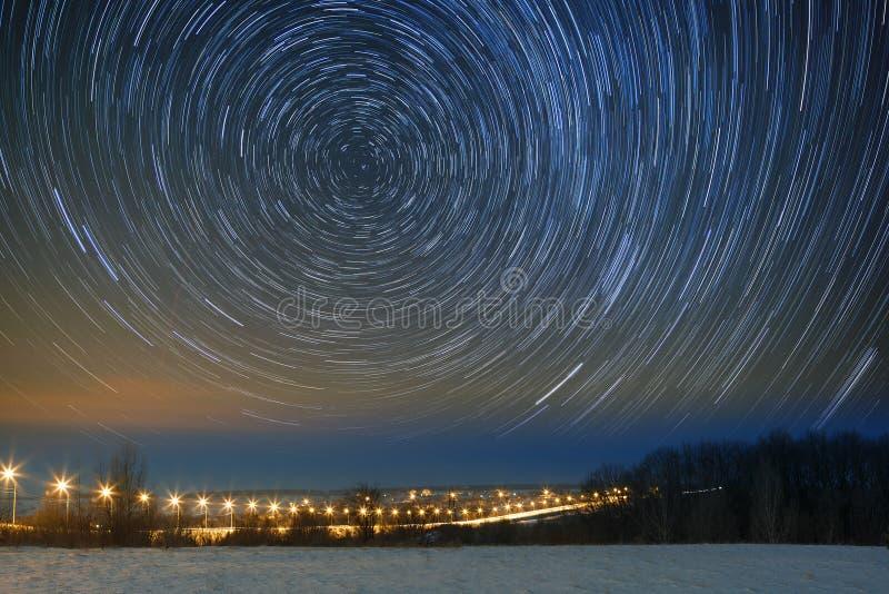 Piste della stella su un cielo notturno Lanterne accese strada principale dell'automobile paesaggio fotografia stock libera da diritti