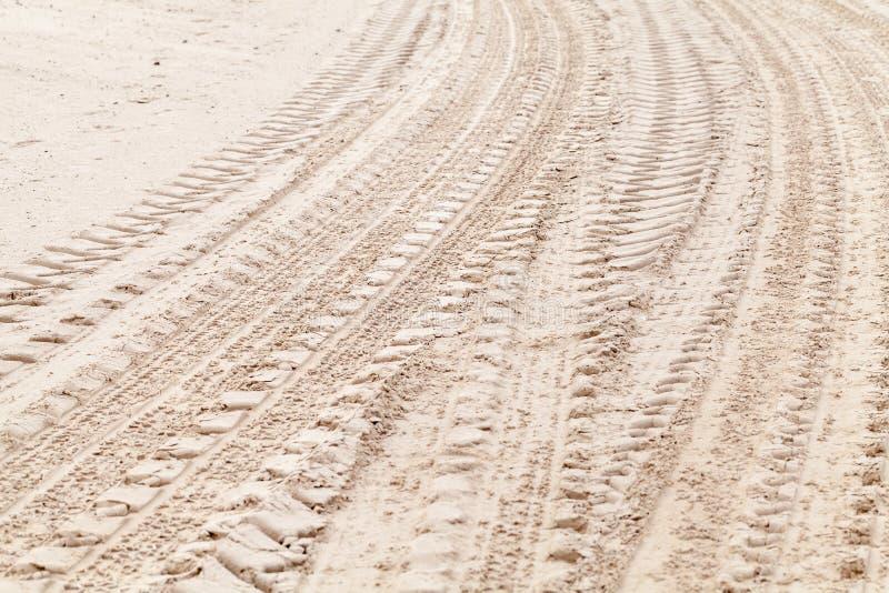 Piste di giro della gomma sulla sabbia bianca immagini stock