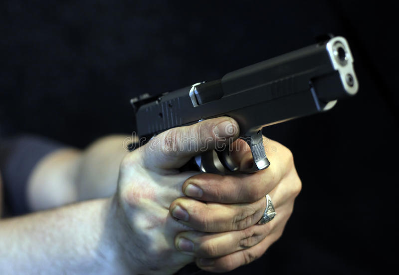 Pistol. Man's hands with a pistol royalty free stock photography