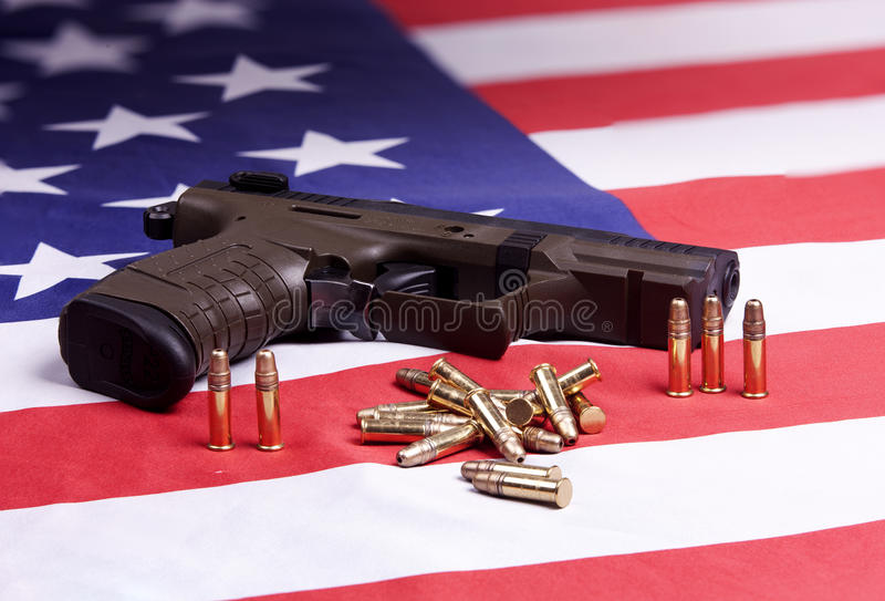 Pistol and ammo on flag. A conceptual image of a pistol and ammo on a US flag royalty free stock photo