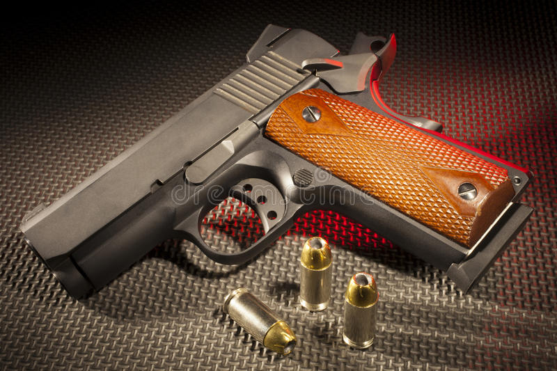 Handgun and ammo with red highlight. Pistol and ammunition on a rubber mat with red lighting royalty free stock photo