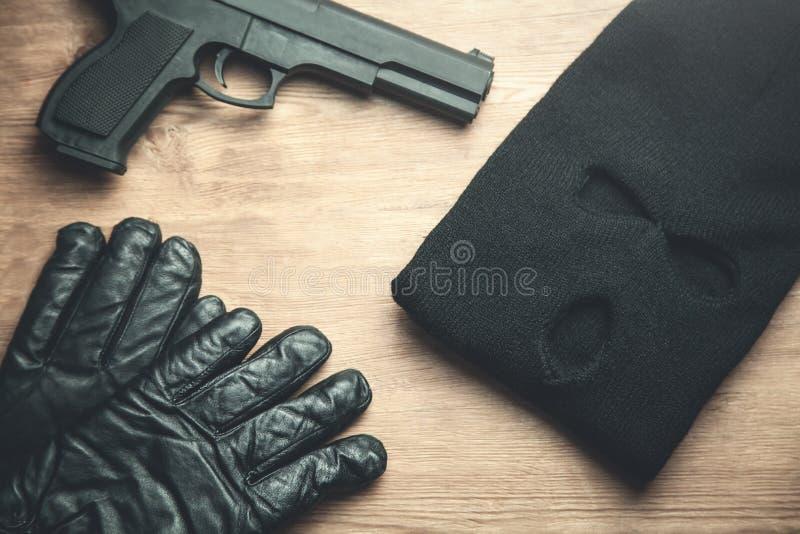Pistol, balaclava och handskar på träbakgrund Conc brottsling arkivbild
