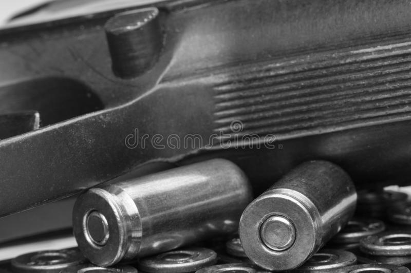 Pistol and bullets close-up isolated on white background. The concept of limiting the spread of small arms. Black and white image. Close-up, background royalty free stock photo