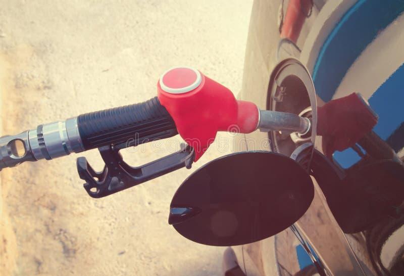 Pistol i bränslet, bil på en bensinstation royaltyfria bilder