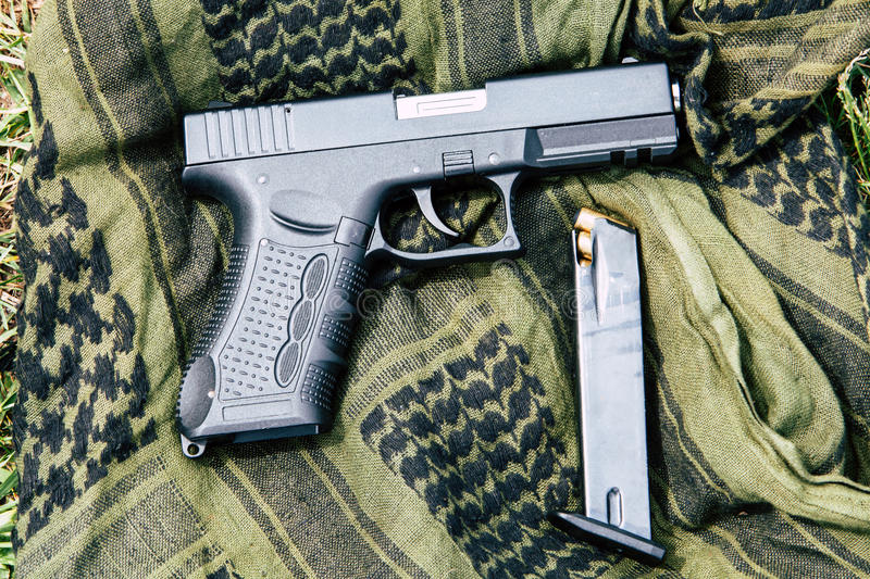 A pistol with a magazine on a green background royalty free stock photo