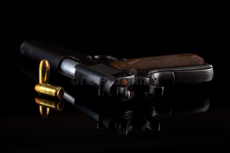 Pistol 1911 med ammunitionar på svart arkivbilder