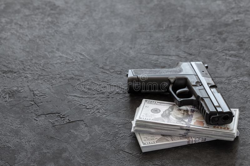 Pistol and money. Guns and dollars on black background. Copy space for text. Pistol and money. Guns and dollars on black background. Copy space for text stock images