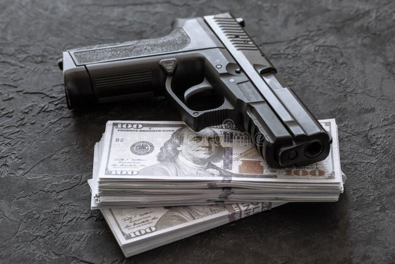 Pistol och pengar Vapen och dollar p? svart bakgrund royaltyfri foto