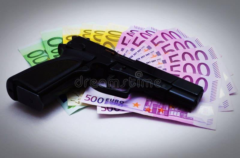 Pistol och sedlar arkivbild