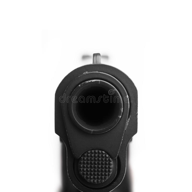 Pistol pointing at a camera. Isolated on white background royalty free stock image