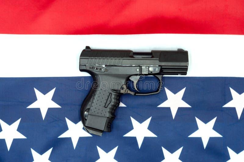 Pistola, bandeira americana e fundo cinzento Leis de Armas dos Estados Unidos - Armas e Armas fotografia de stock
