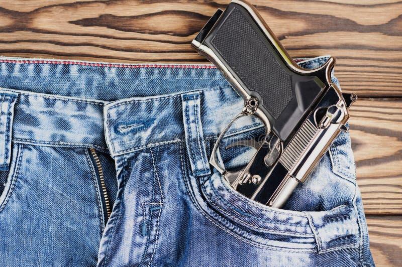 Pistola brillante de la plata del metal en el bolsillo delantero de tejanos en tablones de madera rústicos viejos imagen de archivo libre de regalías