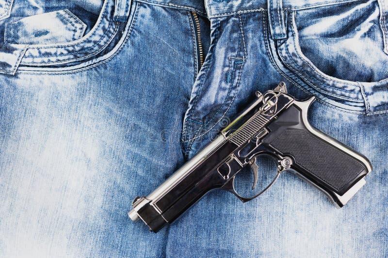 Pistola brillante de la plata del metal en los tejanos imagen de archivo libre de regalías