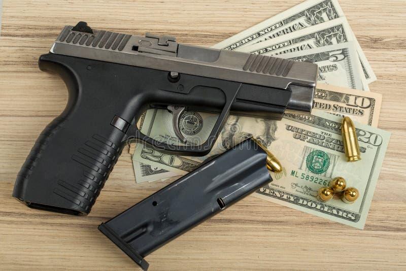 Pistola con la pallottola sulle banconote del dollaro americano immagini stock