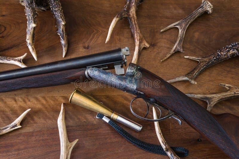 Pistola d'annata di caccia con molti antiers dei cervi fotografia stock libera da diritti