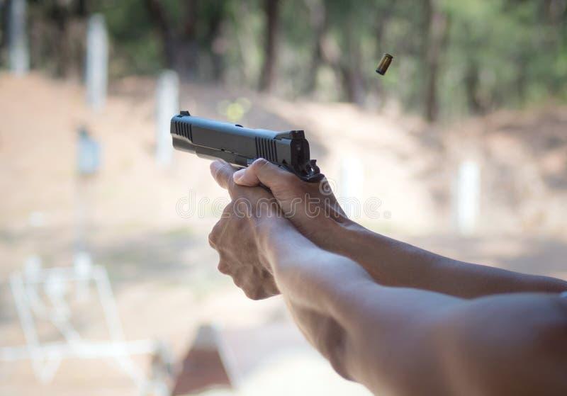 Pistola de la leña del hombre en la gama de leña imagen de archivo libre de regalías