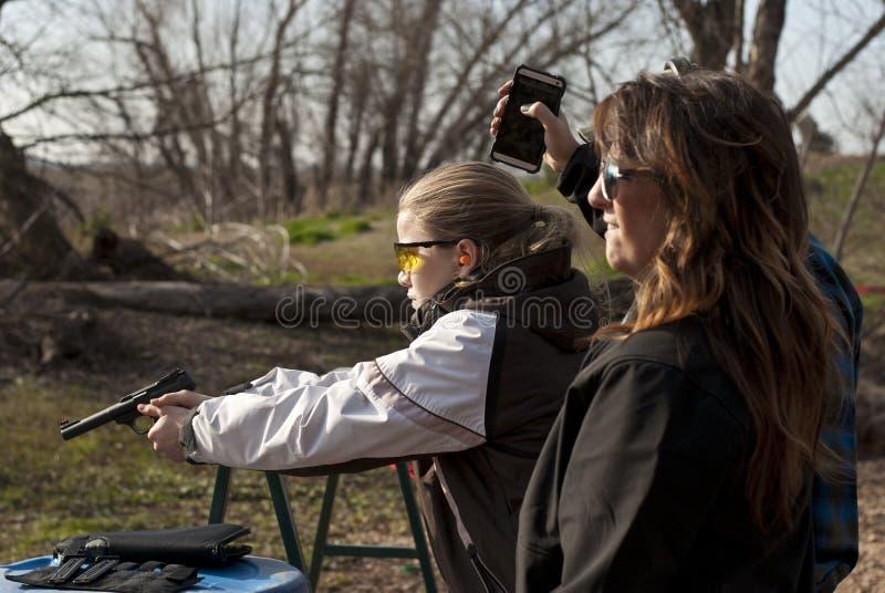 Pistola del tiroteo de la muchacha adolescente con el vuelo de cobre amarillo fotografía de archivo