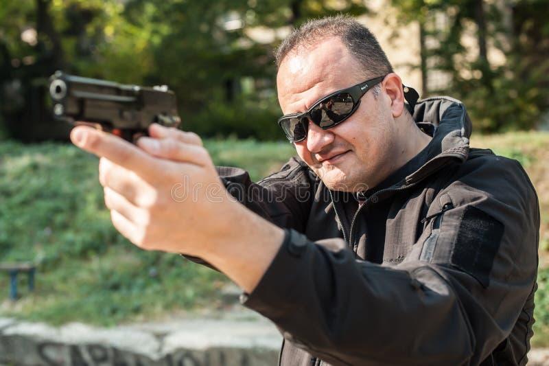 Pistola della guardia del corpo dell'agente di polizia che indica pistola l'attaccante Front View immagine stock libera da diritti