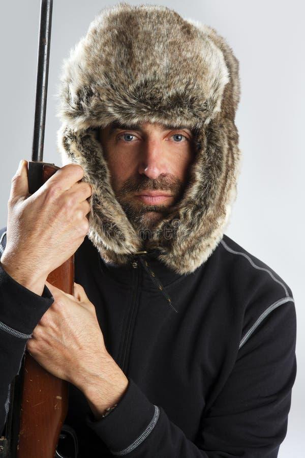 Pistola della holding dell'uomo del cappello di pelliccia di inverno del cacciatore immagini stock libere da diritti