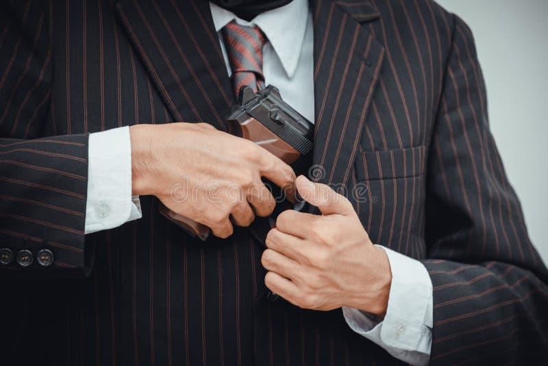 Pistola della tenuta dell'uomo nella sua mano e nella prova nasconderla nella vista del primo piano su fondo bianco fotografie stock