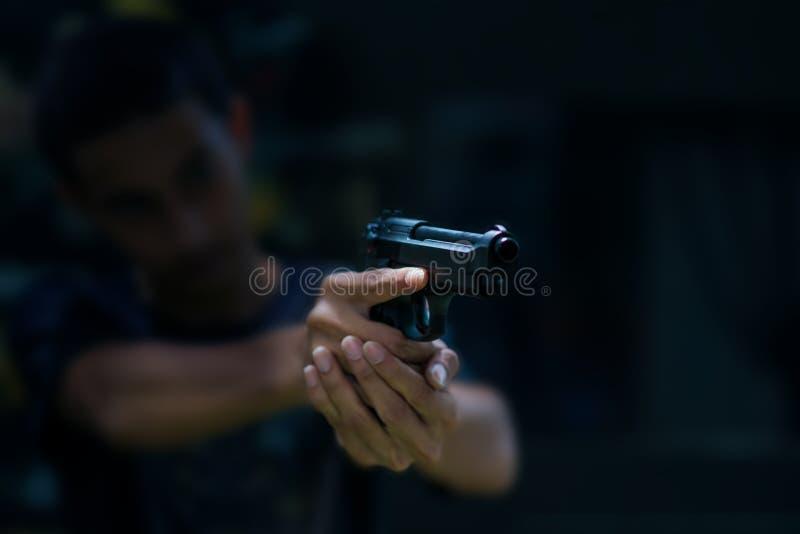 Pistola della tenuta dell'uomo pronta a sparare per proteggere e sicurezza immagine stock libera da diritti