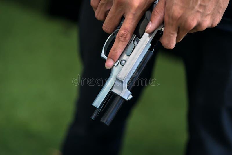 Pistola della tenuta dell'uomo pronta a sparare per proteggere e sicurezza immagini stock libere da diritti
