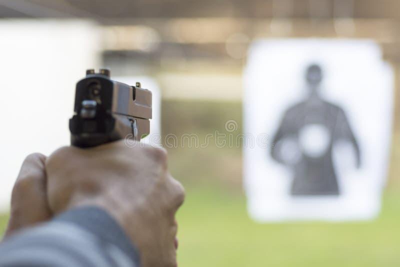 Pistola do acendimento do homem no alvo na escala de tiro fotografia de stock