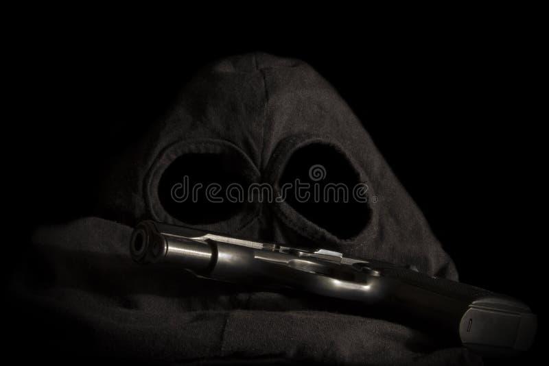 Pistola e máscara de um fundo do ladrão imagem de stock
