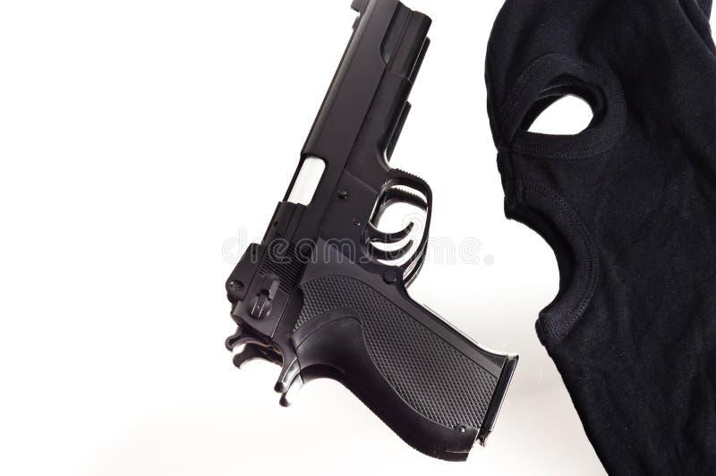 Pistola e máscara de um ladrão fotografia de stock royalty free