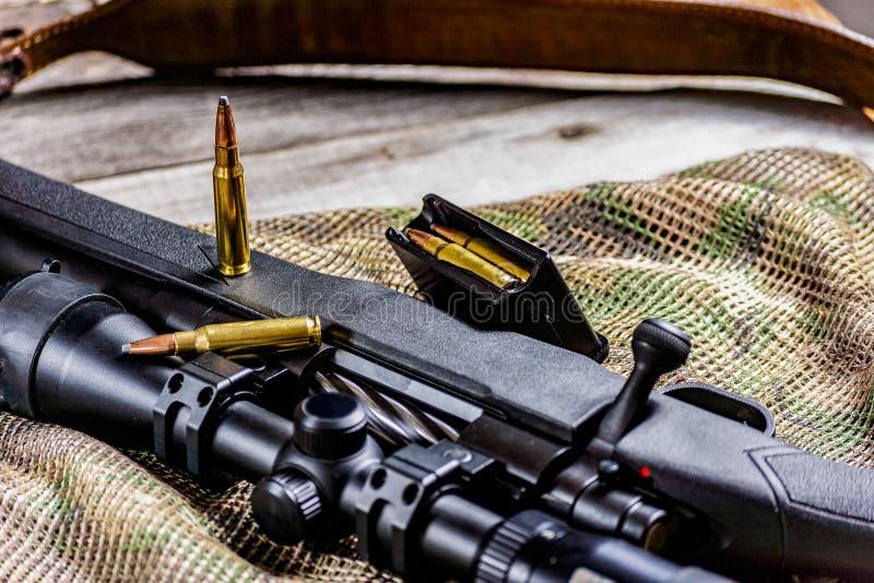 Pistola e munizioni dell'arma del tiratore franco di azione del bullone del fucile sul fondo del multicam immagini stock